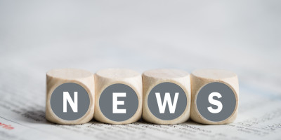 """Wrfel mit dem Wort """"NEWS"""" auf einer Zeitung"""